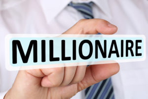 man holding word that says millionaire